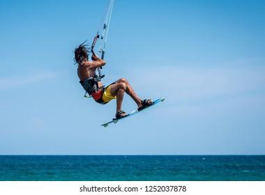 man kitesurfer athlete jumping while performing kite-surfing