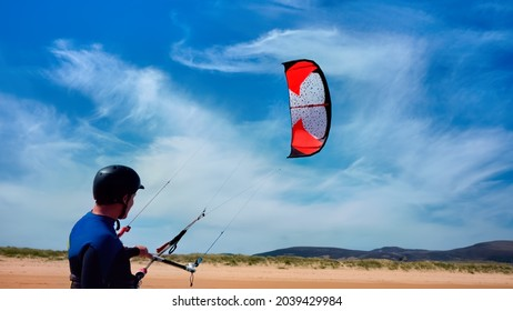 Man kitesurfing or kite boarding sports on Brora beach in the Highlands on a sunny day with blue skies