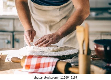 Man kneading and baking homemade pizza dough in the kitchen. Closeup on baker's hands preparing loaf of bread. Cooking and food preparation at home.