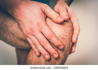 Man with knee pain is holding his aching leg - body pain concept - retro style