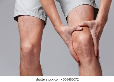 Man  with knee pain on color background