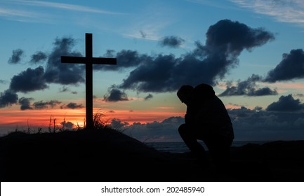 Man kneeling by a cross in prayer as the day finishes.