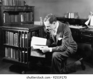 Man kneeling in his home library browsing a book