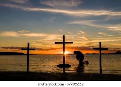 Man kneeling ion prayer at three crosses at sunset