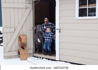 Man kneeling next to happy smiling young son and very tall and muscular male blue great Dane in the open door of a garden shed in winter