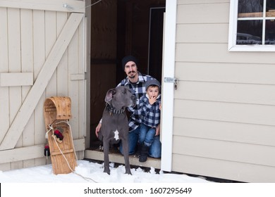 Man kneeling next to young son and very tall and muscular male blue great Dane in the open door of a garden shed in winter