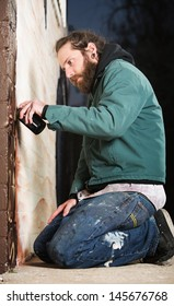 Man kneeling on the ground while spray painting a wall