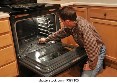 A man kneeling on the kitchen floor and cleaning the inside of an oven.