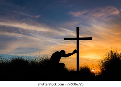 Man kneeling on top of a hill touching a cross at sunset.