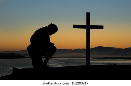 A man kneeling in prayer by a cross on a hill at dawn of a new day.
