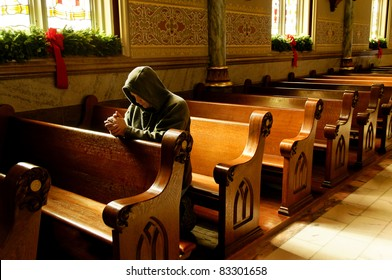 A man kneeling and praying at a church at Christmas time.