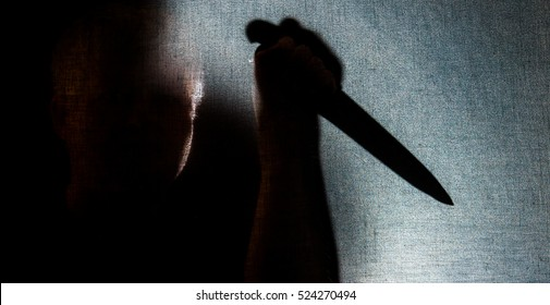 A man with a knife in the backlight