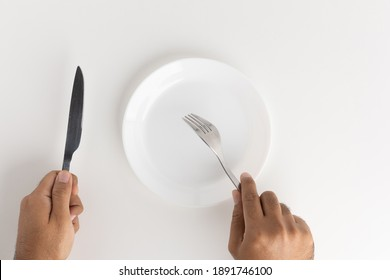 A man with a knife and fork to eat on the plate
