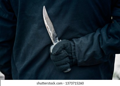 Man with the knife. Hand with a knife behind his back. Criminal with knife weapon hidden behind his back