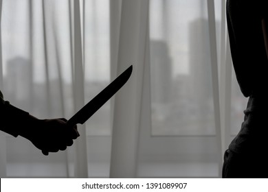 man with a knife in his hands is ready to stab in the back to a woman, partner, wife