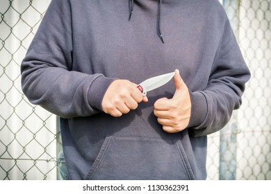Man with knife near fence