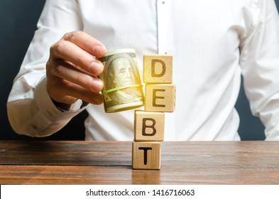 A man knocks down the tower with the word debt with the help of a bundle of money. Early repayment of the loan, remove interest charges and pay only the loan body. Exemption from microcredit.
