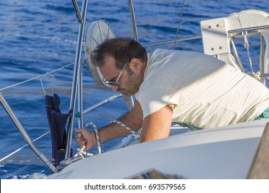 A man is knotting the white rope. He has white to and sunglasses