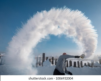 the man from the ladle pours the boiling water up into the sky in an arc in freezing weather when temperature is -48 degrees, the boiling water instantly kristallizuetsya mikimi and scattered crystals