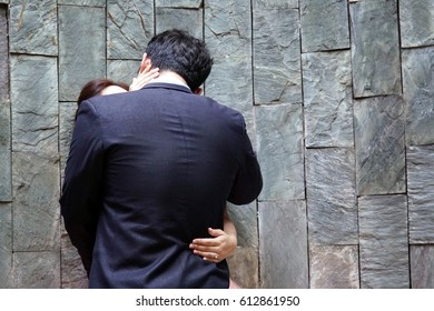 man and lady hug and kiss during wedding on the stone wall