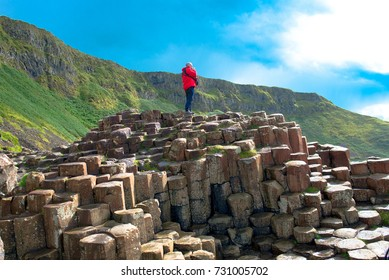 A man in a Landscape of Giant's Causeway trail with a blue sky in summer in Northern Ireland in United Kingdom. UNESCO heritage.