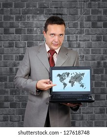 man with a laptop in hand points to world map on screen