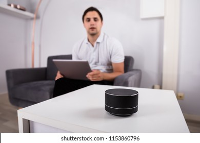 Man with laptop listening to music on wireless speaker at home