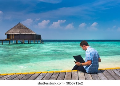 man with laptop and mobile sitting on a wooden bridge near the water bungalows, of background colorful beach of island
