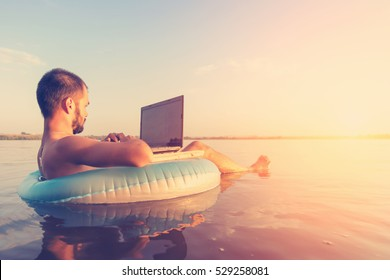 Man with a laptop on inflatable ring in the water