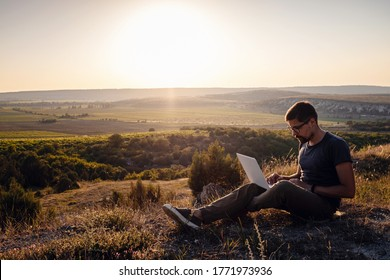 man with laptop sitting on the edge of a mountain with stunning views of the valley. Cellular network broaband coverage concept. 5G.