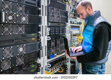 A man with a laptop stands in the server room. A technician works near the racks of a modern data center. The system administrator configures the computer hardware.