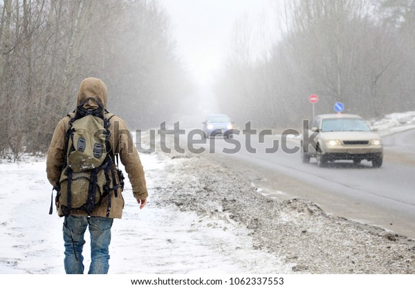 A man with a large backpack walks along a suburban asphalt road in the wintertime during a blizzard