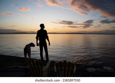 Man with large breed dog enjoying a tranquil sunset by the sea with adult beverage on arm of chair.