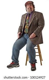 Man with large build sits on stool, dressed casually in tweed cap, jacket and jeans. He leans back and laughs. Vertical, isolated on white background, copy space.