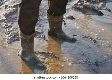 A man in large dirty rubber boots is standing in a dirty spring puddle