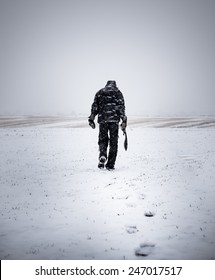 A man with a large knife is walking wasteland in a snowstorm to nowhere.
