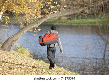 Man  with large sport bag going for outdoor training in park - back view
