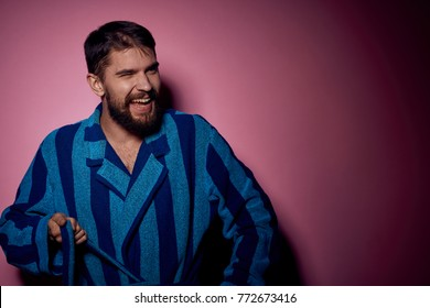 the man is laughing in a blue dressing gown on a pink background, the house