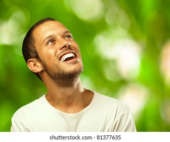 man laughing looking up against a plants background