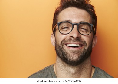 Man laughing in orange studio, close up