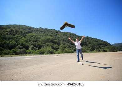 Man launches fixed wings drone with his hands on a road construction site