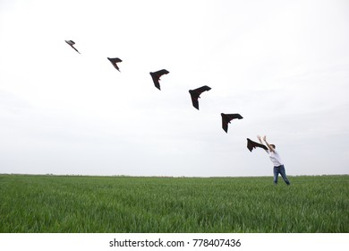 Man launches the fixed wings drone over green wheat field for aerial imaging of crops. Several drone positions visible along the launch path.