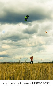 A man launches a kite against the cloudy sky.