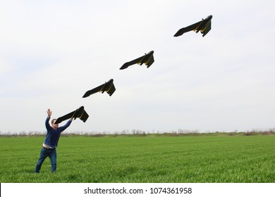 Man launches professional fixed wings drone with his hands, while standing in a green wheat field. Several drone positions visible along the launch path.