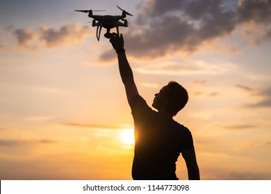 The man launching a quadrocopter on the sunrise background