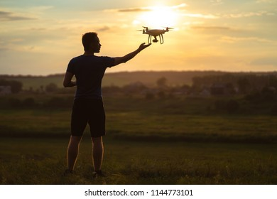 The man launching a quadrocopter on the sunset background
