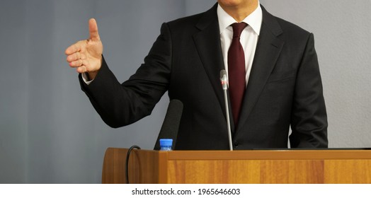 A man - a lawyer, politician, businessman or official speaks from the rostrum. Gesture and microphone. No face