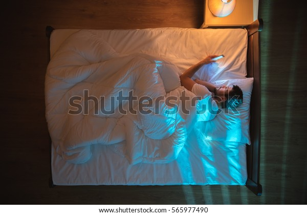 The man lay on the bed and set alarm at night. View from above