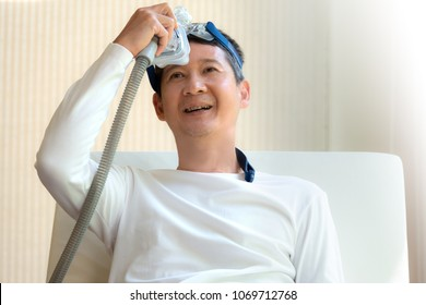 Man laying in bed holding CPAP mask with a smiling face after waking up from daytime sleepiness,front view upper body.Obstructive sleep apnea therapy.