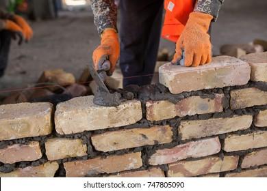 The man is laying bricks